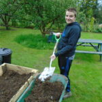 Young man with spade and compost