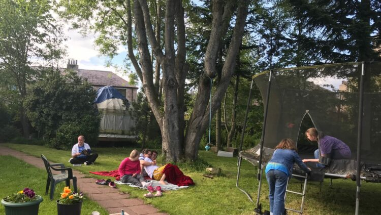 Group of residents having a picnic in the garden and playing on trampoline