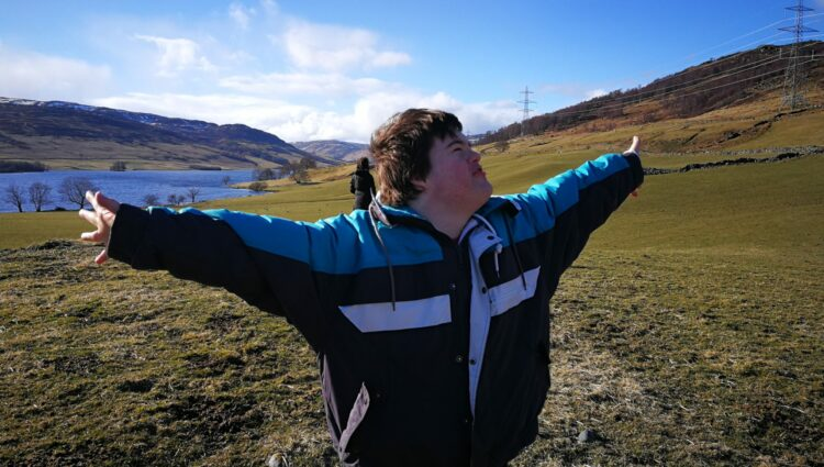 Walker by hills and loch, arms wide open and smiling