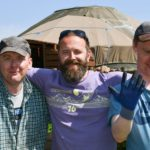 milltown residents together outside group yurt