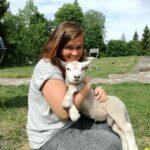Emma cuddling a lamb